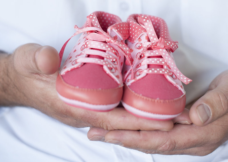 Hands holding a pair of pink, children shoes